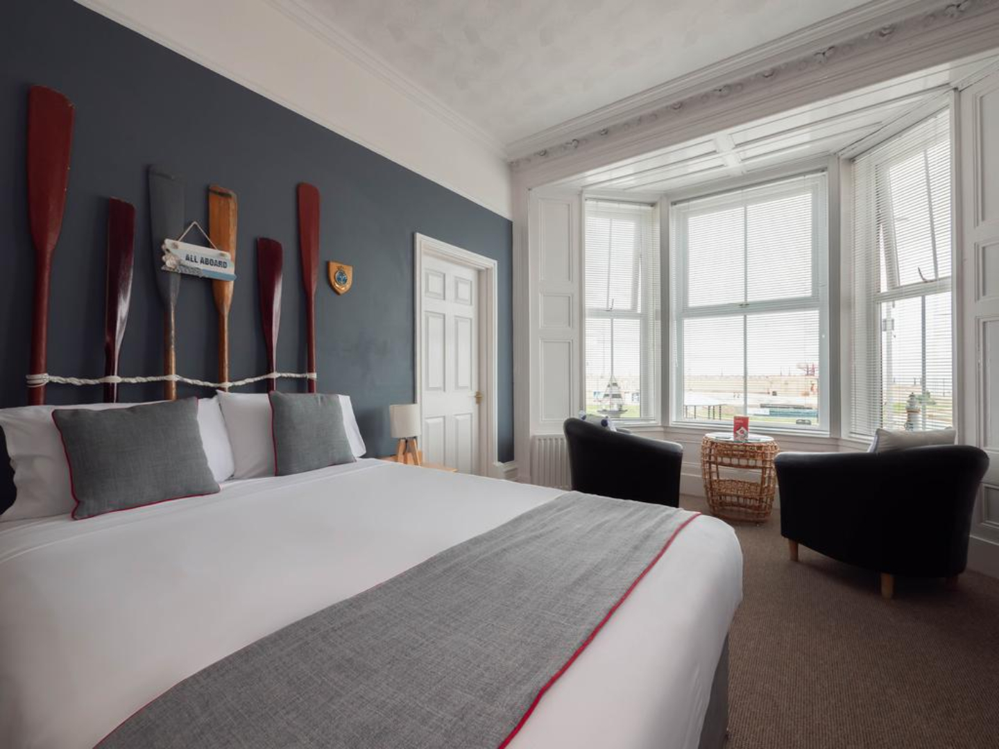 A hotel room with a bed and a large window at The Pier Hotel.