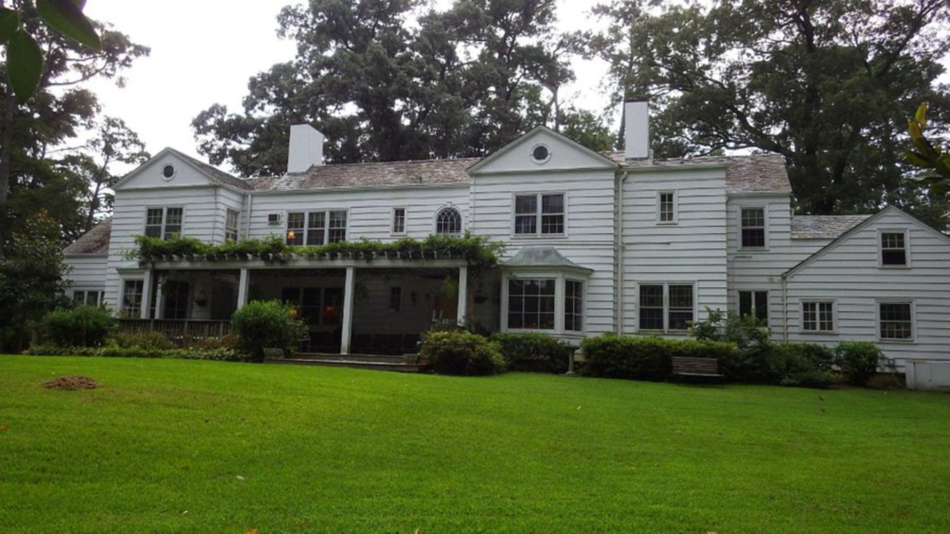 A large lawn in front of a house at The Pond House Inn.