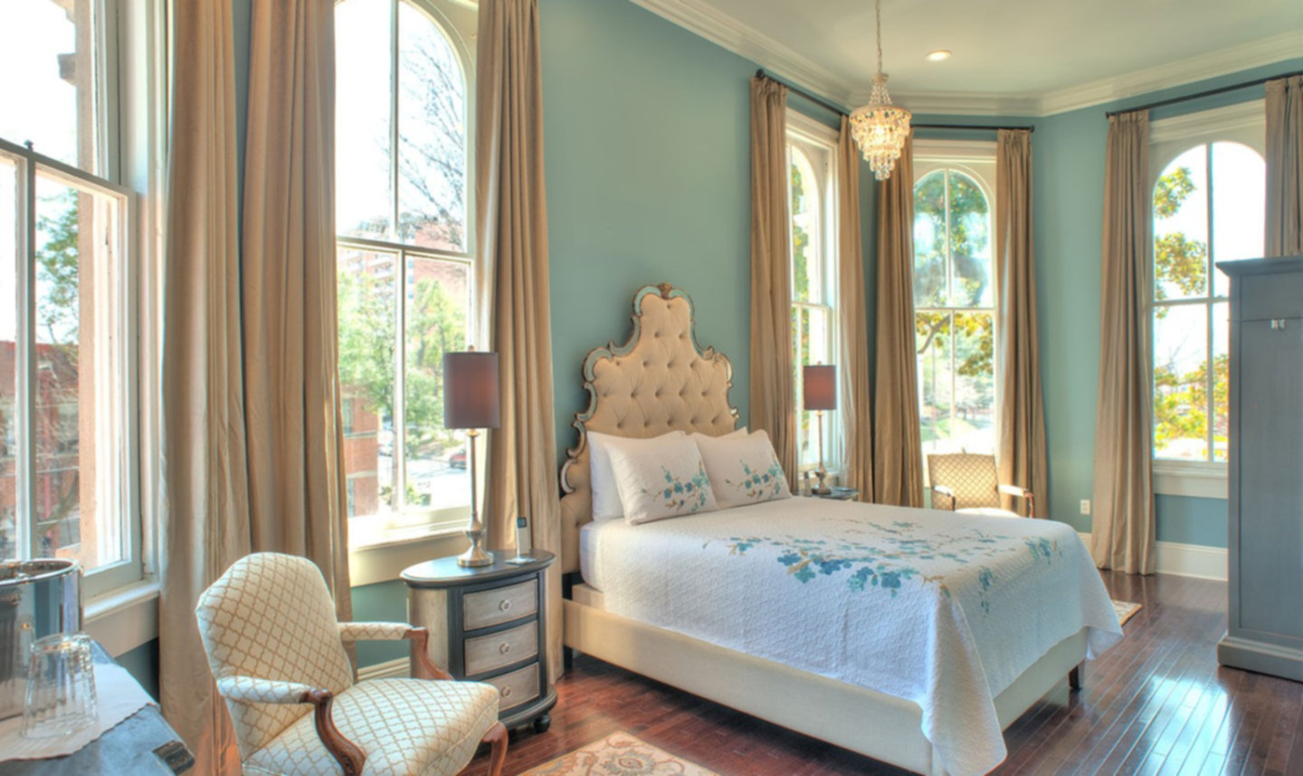 A bedroom with a bed and a large window at The James Lee House.
