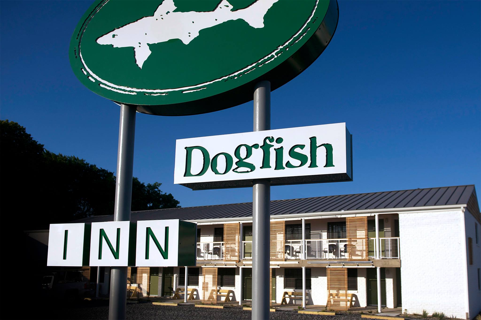 A sign on a pole in front of a building at Dogfish Inn.